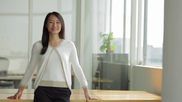 MS SELECTIVE FOCUS Businesswoman leans on table and smiles at camera / Singapore