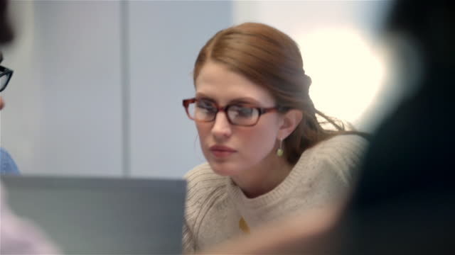 Businesswoman leans over to inspect neighbor's laptop in corporate boardroom meeting