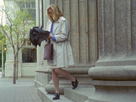 vídeos de stock e filmes b-roll de businesswoman leaving building, opening umbrella - trabalhadora de colarinho branco