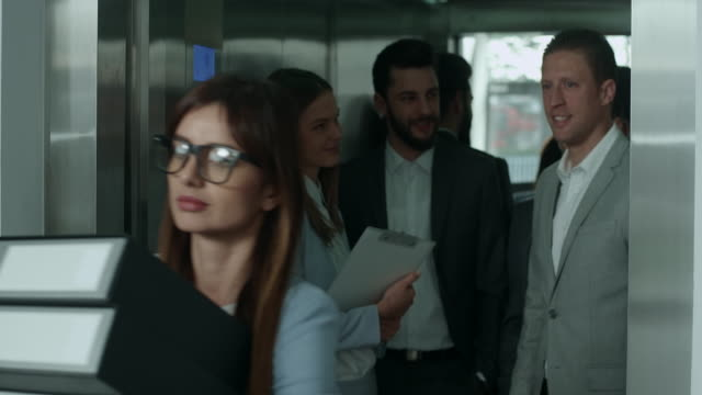 businesswoman leaving elevator - femmina con gruppo di maschi video stock e b–roll