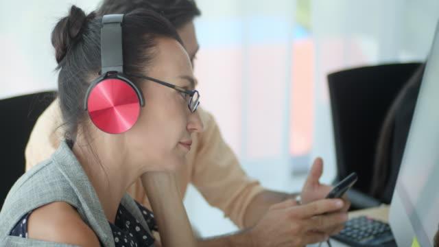 stockvideo's en b-roll-footage met onderneemster die aan muziek luistert en haar hoofd schudt, close-up - in ear koptelefoon