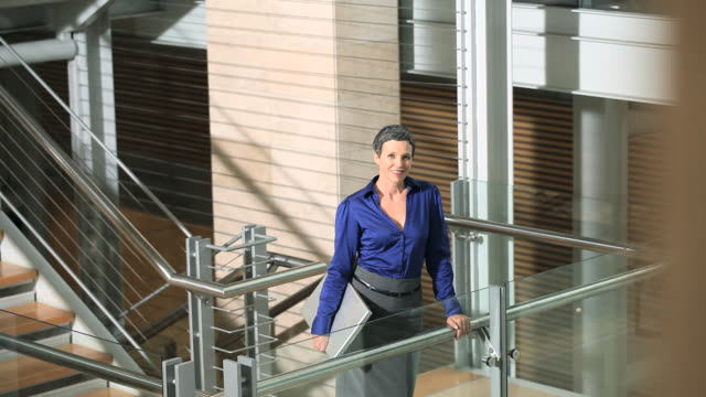 businesswoman looking at camera and walking up stairs - bluse stock-videos und b-roll-filmmaterial
