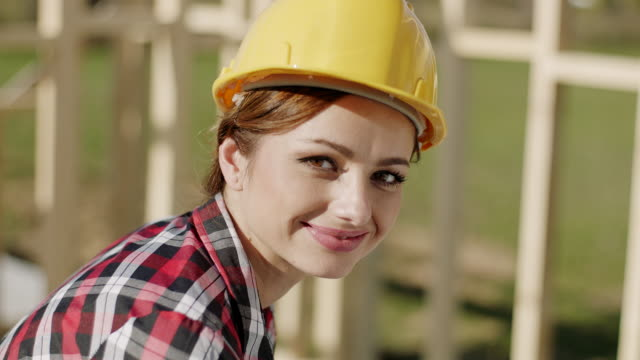 Businesswoman looking at camera at construction site