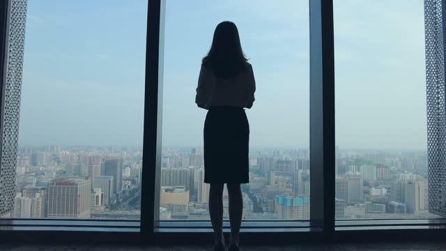geschäftsfrau schaut durch bürofenster auf die skyline der stadt - fensterfront stock-videos und b-roll-filmmaterial