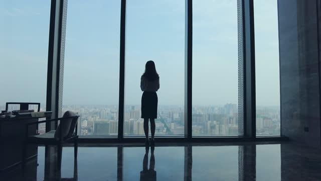 vídeos de stock, filmes e b-roll de empresária olhando para o horizonte da cidade através da janela do escritório - telhado