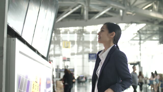 businesswoman looking at timetable departure board at airport - airport terminal stock videos & royalty-free footage