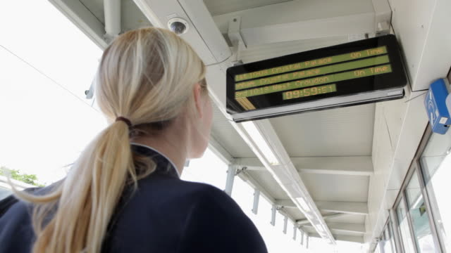 businesswoman looking at train departure board - ponytail stock videos & royalty-free footage