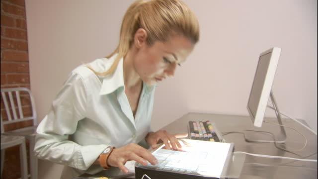 ms zi cu businesswoman looking at transparencies in lightbox, then two businessmen enter office and discuss project / los angeles, california, usa  - skjorta och slips bildbanksvideor och videomaterial från bakom kulisserna