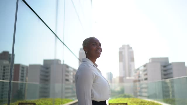 vidéos et rushes de femme d'affaires regardant loin contemplant et pensant sur le toit de bureau - directrice