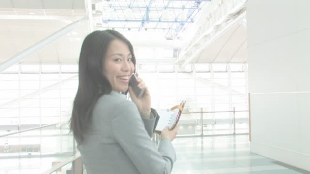 Businesswoman looking back smiling as talking on cellular phone