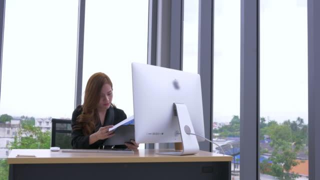 vídeos de stock, filmes e b-roll de mulher de negócios olhando no relatório de trabalho de bloco de nota. jovem empresária asiática, usando telefone - note pad
