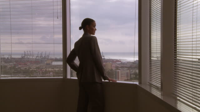 businesswoman looking out window over port - businesswoman stock videos & royalty-free footage