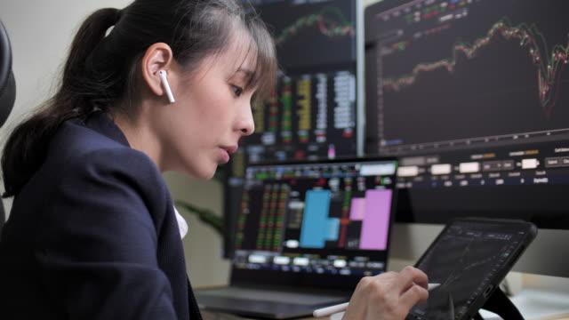 vídeos y material grabado en eventos de stock de empresaria buscando smartphone y pantalla financiera del mercado de valores - vigilante