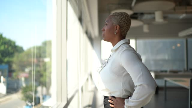 businesswoman looking through window contemplating and thinking on the office - motivation stock videos & royalty-free footage