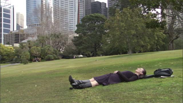 vídeos y material grabado en eventos de stock de ms, businesswoman lying on lawn in park, office buildings in background, sydney, australia - acostado