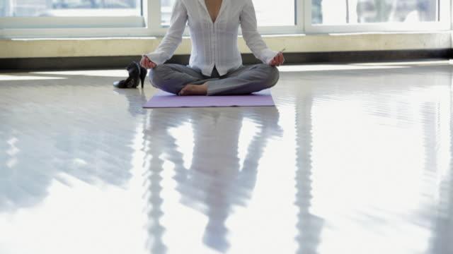 WS TU Businesswoman meditating in office / Vancouver, British Columbia, Canada