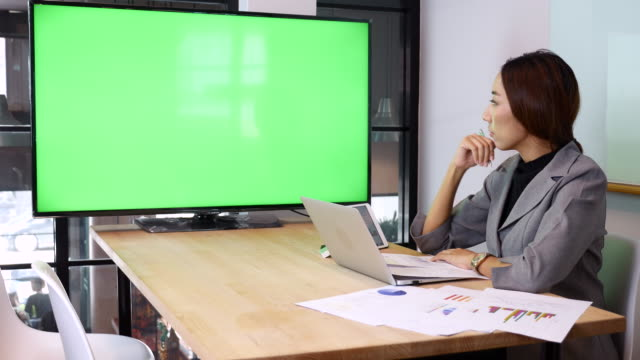 Businesswoman Meeting with Video conference on TV Monitor green