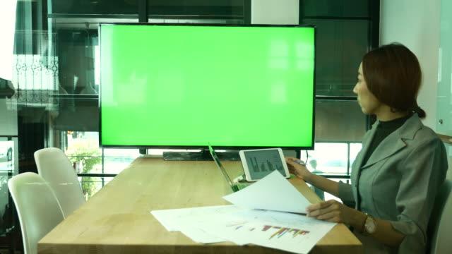 Zakenvrouw ontmoeting met videoconferentie op televisiescherm groen scherm