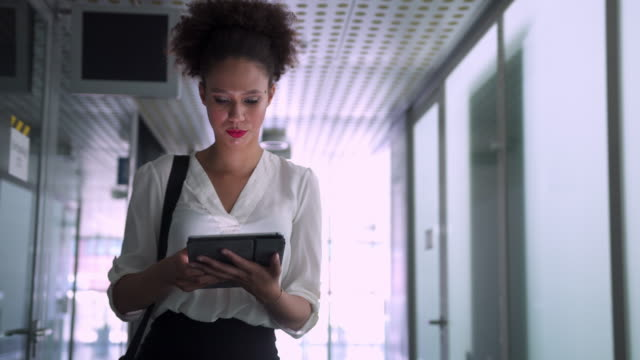 businesswoman on her digital tablet on hallway - digital tablet stock videos & royalty-free footage