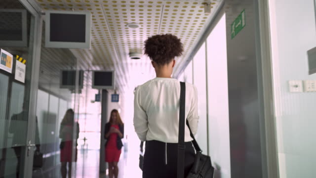 Businesswoman on her phone on hallway