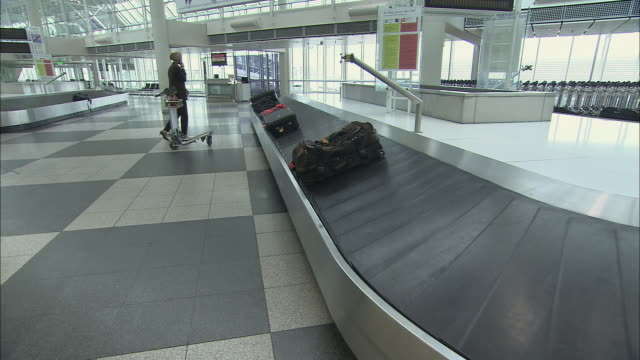 WS Businesswoman on mobile phone removing suitcases from baggage claim carousel and putting on luggage cart / Munich, Germany