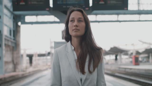 vidéos et rushes de businesswoman on train platform holding cell phone - quai de gare