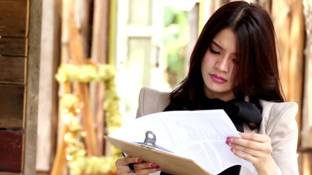 donna d'affari aperto documento e verifica le informazioni - direttrice video stock e b–roll