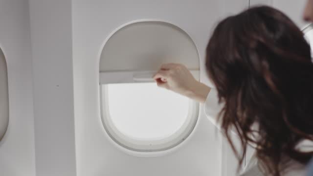 stockvideo's en b-roll-footage met onderneemster die venster van vliegtuig opent - moving activity