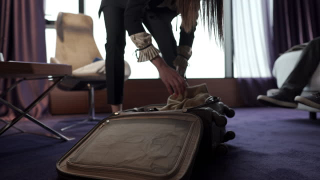 businesswoman organising her luggage while relaxing in a hotel suite - upper class stock videos & royalty-free footage