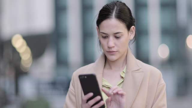 businesswoman outdoors in city using smartphone - 保険点の映像素材/bロール