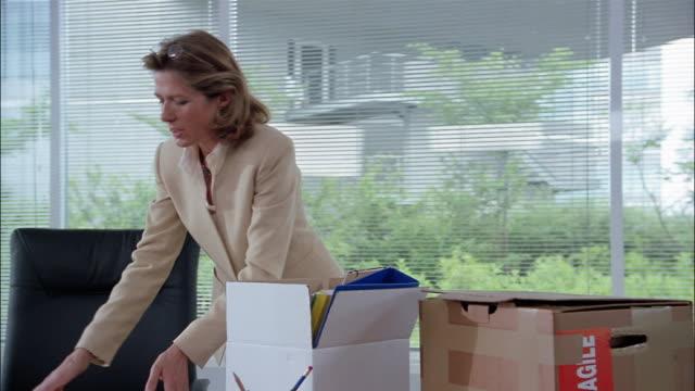 stockvideo's en b-roll-footage met a businesswoman packs boxes on her desk. - ontslaan