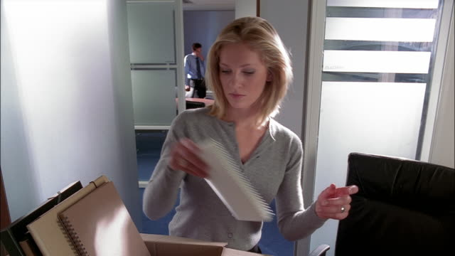 a businesswoman packs her belongings into a box and leaves her office. - unemployment stock videos and b-roll footage