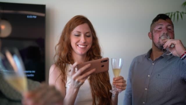 vídeos y material grabado en eventos de stock de empresaria fotografiando o haciendo un video chat en la fiesta de celebración en la oficina - evento virtual