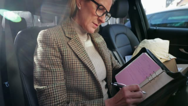 businesswoman planning in the car - well dressed stock videos & royalty-free footage