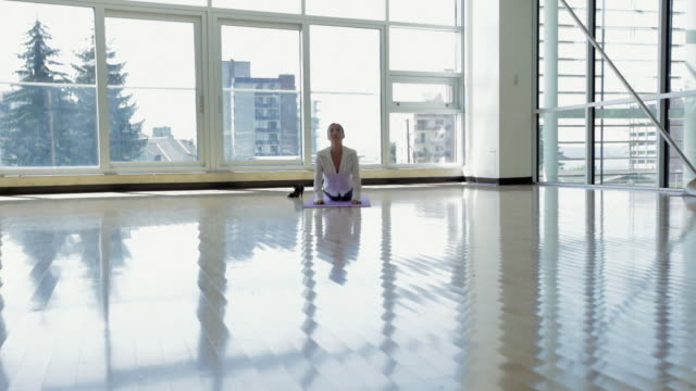 WS Businesswoman practicing yoga in office / Vancouver, British Columbia, Canada