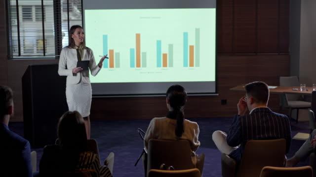 stockvideo's en b-roll-footage met onderneemster die een bedrijfsstrategiepresentatie aan een professioneel publiek voorstelt - diavoorstelling