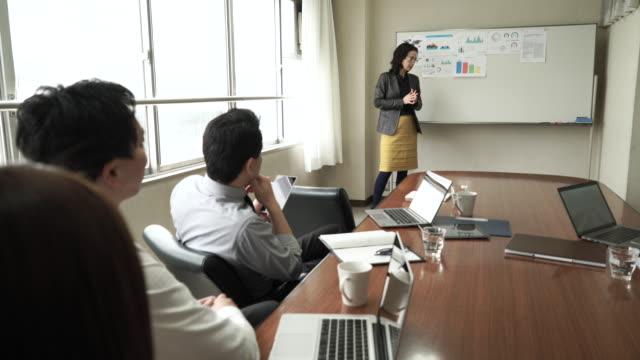 vidéos et rushes de femme d'affaires présenter dans la salle de réunion - tenue d'affaires formelle