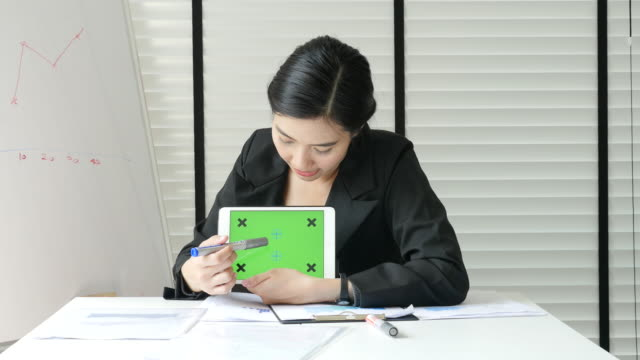 Businesswoman presenting Tablet PC with Green screen