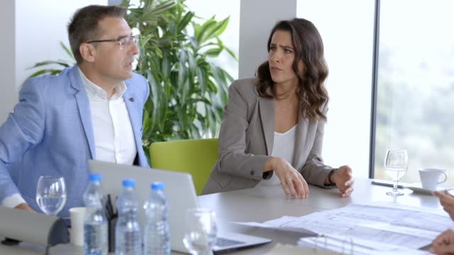 vidéos et rushes de femme d'affaires proposant une nouvelle stratégie à son équipe, expliquant et faisant des gestes - table de salle de réunion
