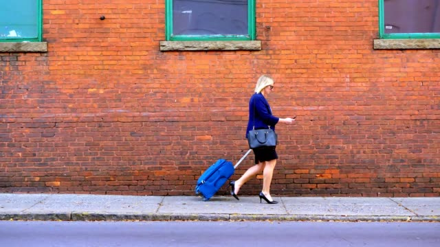 businesswoman pulling suitcase down sidewalk in city. - sidewalk stock videos & royalty-free footage