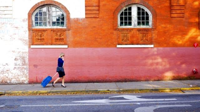 Geschäftsfrau Koffer Gehweg in die Stadt ziehen.