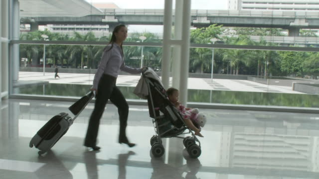 ms ts businesswoman pushing daughter (2-3) sitting in baby stroller through lobby / bangkok, thailand - working mother stock videos & royalty-free footage