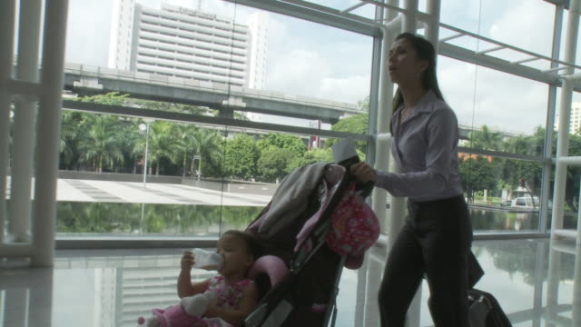 ms ts businesswoman pushing daughter (2-3) sitting in baby stroller through lobby / bangkok, thailand - pushchair stock videos and b-roll footage