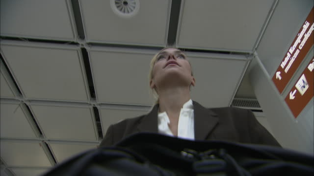 stockvideo's en b-roll-footage met la ms businesswoman pushing luggage cart in airport, then answers her mobile phone / munich, germany - münchen vliegveld