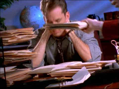 FAST businesswoman puts folder on businessman's messy desk / man puts his head down in frustration