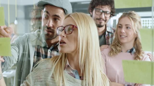 実業家は、ガラスの壁に付箋を置く - スクラム点の映像素材/bロール