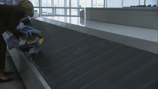 stockvideo's en b-roll-footage met la ms businesswoman putting clothing back into open suitcase on baggage claim carousel / munich, germany - münchen vliegveld