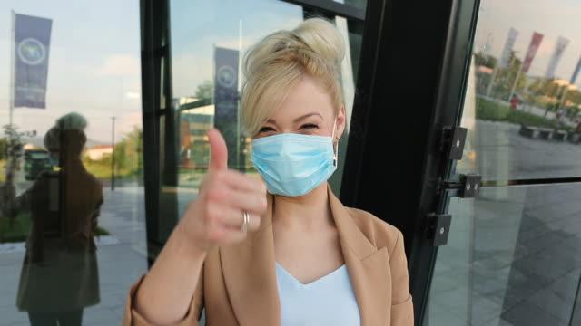 geschäftsfrau setzt schutzbeschützende gesichtsmaske auf und zeigt daumen nach oben vor dem bürogebäude - weibliche angestellte stock-videos und b-roll-filmmaterial