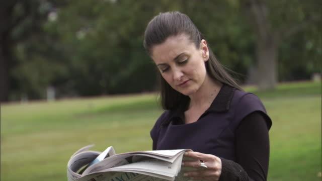 cu, businesswoman reading newspaper in park, , sydney, australia - newspaper stock videos & royalty-free footage