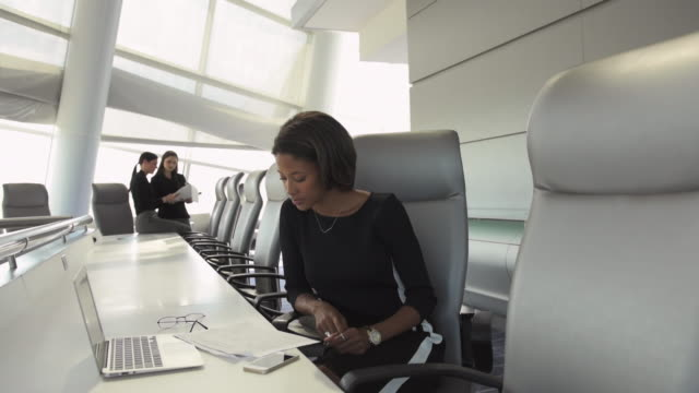 businesswoman reading paperwork and using laptop in conference room - mittellanges haar stock-videos und b-roll-filmmaterial